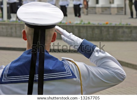Navy soldier salutes at the lithuanian national flag ceremony