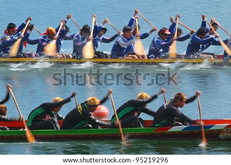 NAYOK, THAILAND - DECEMBER 3: A pair of unidentified traditional Thai long boats with a crew of 50 compete Chakri Sirindhorn Cup, a champion long boat race, on December 3, 2011 in Nayok, Thailand.
