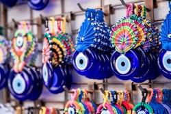 Nazar boncuk amulets (wards against the evil eye) hanging in the row at grid, Arasta Bazaar, Istanbul. Closeup shot