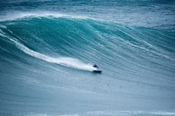 NAZARE, PORTUGAL - surfer riding a large wave  at Praia do Norte - Nazare, Portugal.