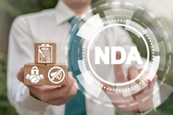 NDA Non-Disclosure Agreement Business concept. Man holding wooden cubes with confidentiality icons and pushing nda acronym virtual button.
