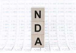 NDA - non disclosure agreement - text on wooden cubes, on light background