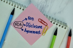 NDA - Non Disclosure Agreement write on sticky note isolated on Wooden Table. Selective focus on NDA - Non Disclosure Agreement text