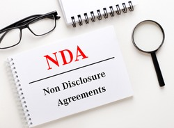 NDA Non Disclosure Agreements is written in a white notebook on a light background near the notebook, black-framed glasses and a magnifying glass.