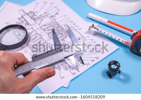 Ndt inspector or an expert is analysing pump blueprints before performing control operations.