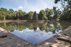 Neak Pean is built in the middle of artificial lake and surrounded by tropical forest on beautiful blue sky, calm water, reflection on water. small temple but magnificent