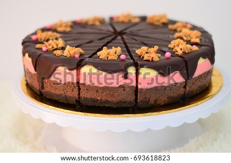 Neapolitan cheesecake cut into slices. Neapolitan cheesecake consist of four layers of biscuit base, chocolate layer, strawberry layer and vanilla layer. #693618823