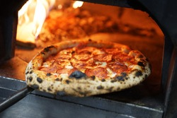 Neapolitan pizza with sausage in a wood-fired oven