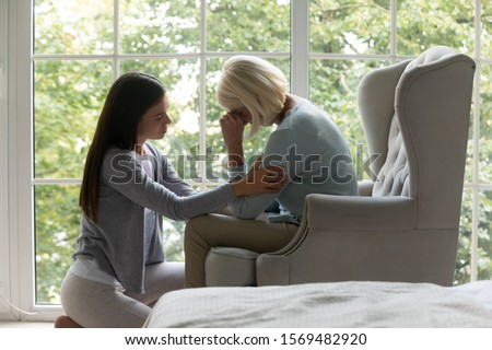Near panoramic window crying elderly mom sit on armchair, near sit her grown up daughter comforting her in difficult life period give support, share pain at divorce, showing attention and care concept