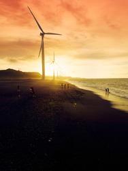 Near Silhouettes of wind turbines agaisnt the sun during sundown at Bangui, Ilocos Norte Philippines. A tourist spot near Pagudpud. Great picture for renewable energy topics