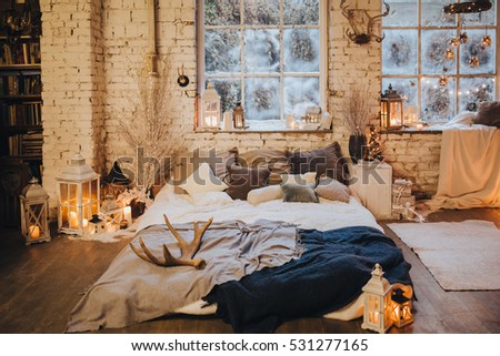 near snowy window is the bed with pillows and blankets, there are a number candles, Christmas decorations and Garlands #531277165
