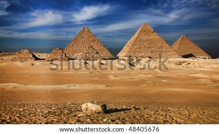 Near to the city of Cairo, in Sinai desert, against the pure blue sky and clouds, pyramids, an ancient miracle of the world have settled down