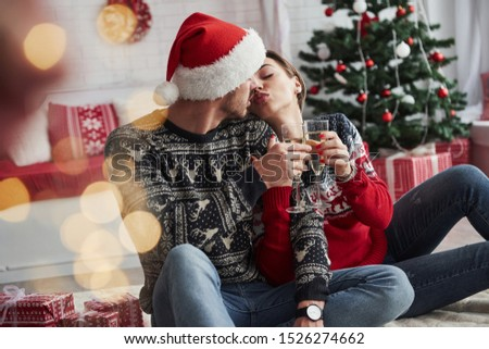 Nearly kissed. Two people sits on the floor and celebrate new year.