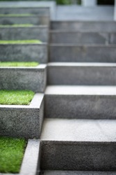 Neat and tidy grey stair steps made of stone and granite tiles with a curb, side by side with green steps in a modern hotel leading to a lobby area, close up.