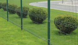 neat metal fence and bushes of a park zone in the city