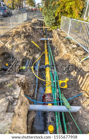 Neat orderly organised cables, pipes and sewage under pedestrian walkway during renovation of the infrastructure system. Netherlands