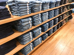 Neat stacks of folded jeans on the shop shelves in the showroom or store. Clothes storage.