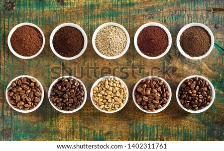 Neat still life of assorted varieties of ground coffee and medium, full and mild roasted beans in individual bowls on a rustic wood background viewed top down in two rows #1402311761