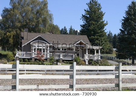 neat suburban house with a white fence in the foreground