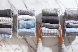 Neatly folded clothes and pyjamas in the metal mesh organizer basket on white marble table. Marie Kondo style of garments declutter and sorting concept. Housewife using Konmari method of tidying up.