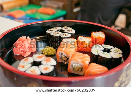 neatly on a platter lined with sushi