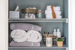 Neatly organized bathroom linen closet with bamboo toothbrushes and white towels