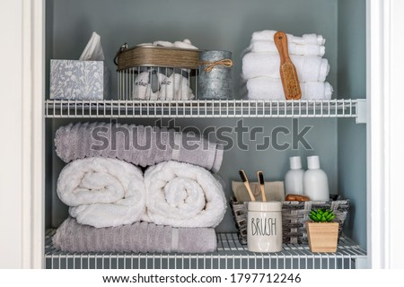 Neatly organized bathroom linen closet with bamboo toothbrushes and white towels Stockfoto ©