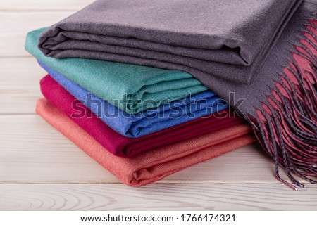 Neatly stacked piles of cashmere stoles, shawls, scarves of different colors. Women's accessory, gift souvenir. Studio shot. Сток-фото ©