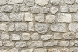 Neatly stacked rough cut stone wall seamless texture background.