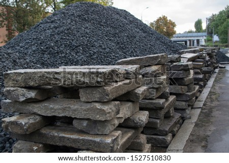 Neatly stacked, stacked on top of each other, old rectangular cement-gray road curbs, lyied in connection with road repairs, against a high mountain of black rubble piled on the centre of the street #1527510830