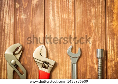 Necessary set of tools for plumbers on a vintage wooden wooden background. Also space for advertising. #1435985609
