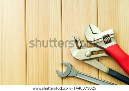 Necessary set of tools for plumbers on a wooden background. Also space for advertising. #1440373025