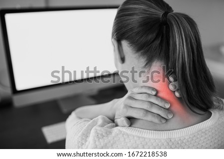 Neck ache concept. Young woman sitting at office desk feeling hurt having pain in her neck.Woman massaging rubbing stiff sore neck tensed muscles, fatigued from computer work and incorrect posture.
