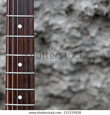 Neck of the guitar on gray background