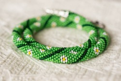 Necklace from beads with flower drawing on a textile background