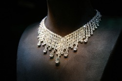 Necklace made of white gold with diamonds on a stand in the dark room