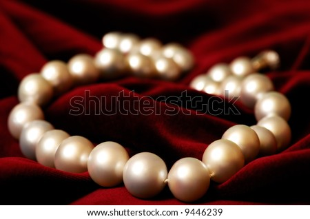 Necklace made out of real pearls on deep red velvet background