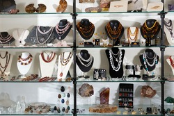 Necklaces, earrings, pendant made of semiprecious stones on display of jewelry store