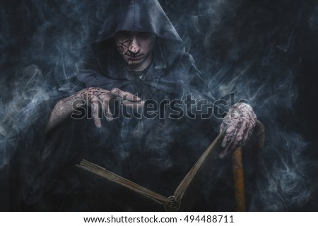 Necromancy sorcerer casting black magic spell using his book of shadows Foto stock ©