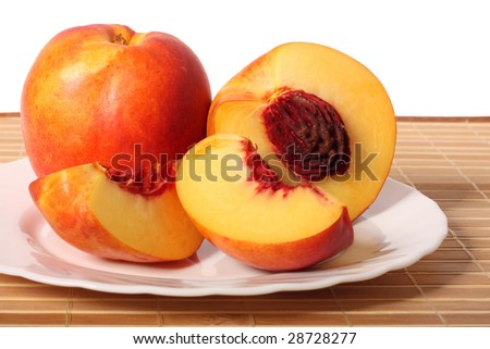 Nectarine fruit, a half and two quarters, on plate, isolated on white background