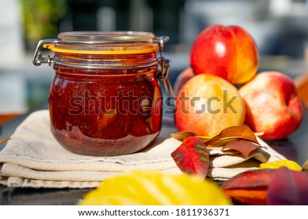 Nectarine jam and fresh nectarines. Homemade nectarine jam with fresh organic nectarines on wooden rustic background. Selective focus.
