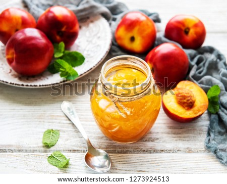 Nectarine jam with fresh nectarines on a white wooden table