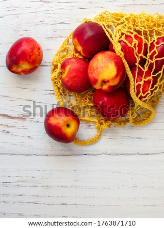 Nectarine. Ripe juicy organic nectarines (peaches) in a reusable mesh cotton shopping bag on a wooden table. plastic free zero waste concept. Selective focus, top view, copy space