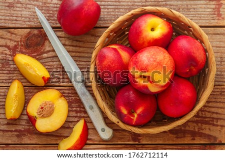 Nectarine. Ripe juicy organic nectarines (peaches) in a wicker basket. Whole and sliced fruit on a wooden table. Selective focus, top view