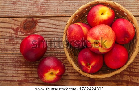 Nectarine. Ripe juicy organic nectarines (peaches) in a wicker basket. Whole fruit on a wooden table. Selective focus, top view, copy space