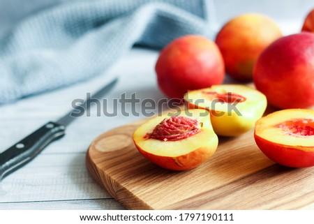 Nectarine. Ripe juicy organic nectarines (peaches) on cutting board. Whole and sliced fruit.