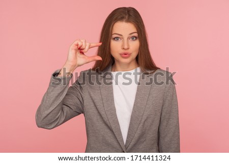 Need some more! Portrait of sceptic displeased young woman in business suit making a little bit gesture, small size, dissatisfied with low rating. indoor studio shot isolated on pink background Сток-фото ©