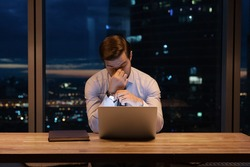 Need some rest. Overworked young man ceo manager take break in online work close tired eyes rub nose bridge. Busy office employee suffer from chronic dry eye syndrome spending hours in front of laptop