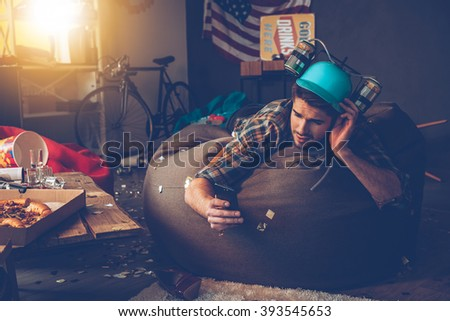 Need to delete that picture! Handsome young man in beer hat using his smart phone while lying on bean bag in messy room after party #393545653