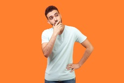 Need to think. Portrait of thoughtful brunette man with beard in white t-shirt holding his chin and pondering idea, confused not sure about solution. indoor studio shot isolated on orange background